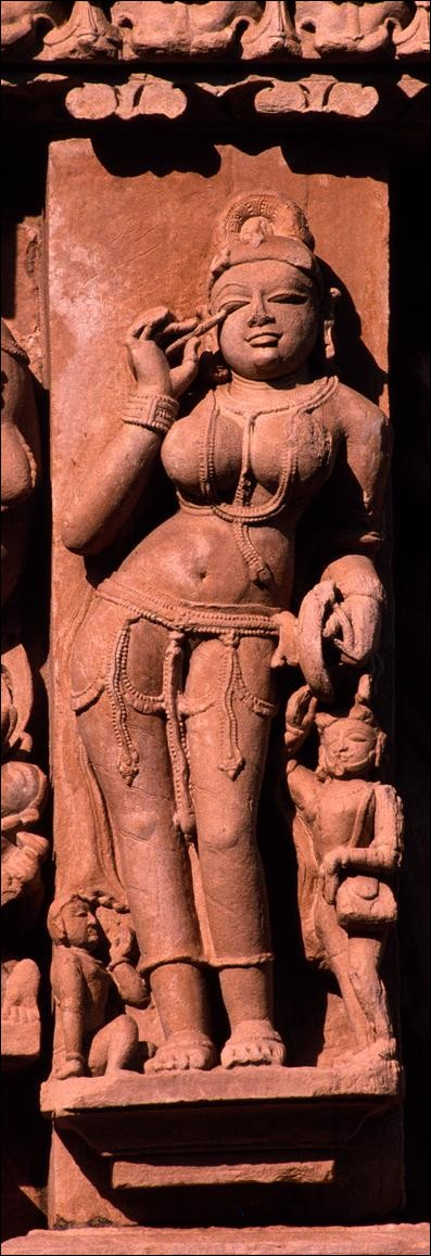 Woman applying eyeshadow, Parsvanath Temple, Khajuraho, India