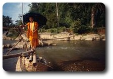 Monk crossing river at Tham Xang near Vang Vieng, Laos